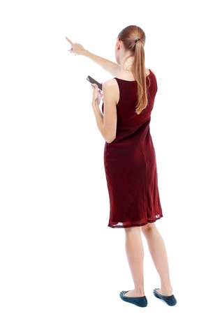 back view of pointing young beautiful girl with tablet computer. Isolated over white background. girl in the maroon sleeveless dress keeps your phone and shows a finger forward.