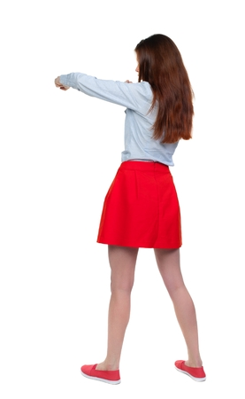 skinny woman funny fights waving his arms and legs. Long-haired brunette in red skirt has a hand.