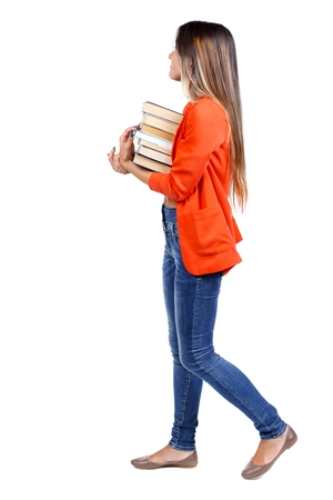 Girl comes with stack of books. side view. girl in a red jacket goes to the side with a stack of books looking at what is to come.