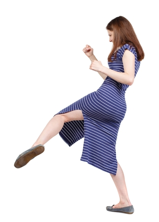 skinny woman funny fights waving his arms and legs. brunette in a blue striped dress has a foot.