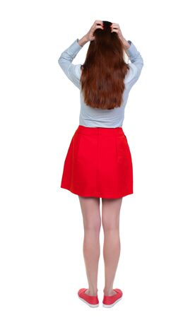back view of standing young beautiful woman. Long-haired brunette in red skirt anxiously holding his head. Stock Photo