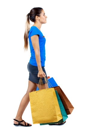 side view of going woman with shopping bags . beautiful girl in motion. girl in a short skirt and a blue T-shirt carries the side paper bags.
