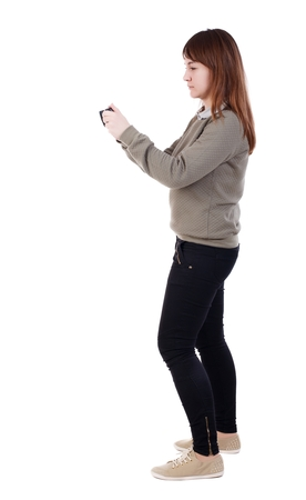 back view of standing young beautiful woman and using a mobile phone. Isolated over white background. A girl in a gray jacket with a disassembled camera settings.