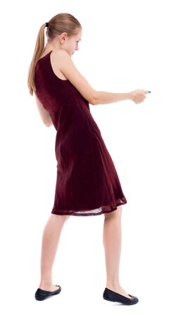 girl in burgundy dress: back view of standing girl pulling a rope from the top or cling to something. Isolated over white background. A girl in a burgundy dress pulling rope side.