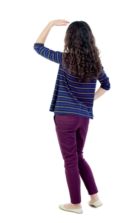 back view of standing young beautiful woman. Long-haired curly girl in a blue jacket stares into the distance somewhere. Stock Photo