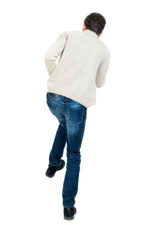wimp: back view of guy funny fights waving his arms and legs. Rear view people collection. backside view of person. Curly short-haired man in a woolen white jacket jumping on one leg.