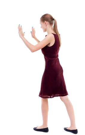 girl in burgundy dress: back view of woman pushes wall. Isolated over white background. girl in a burgundy dress pushing in the side load.