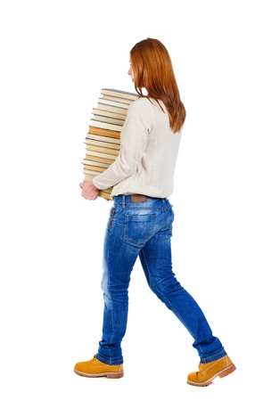warm jacket: Girl comes with stack of books. side view. girl in a white warm jacket bears a huge stack of books