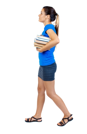 falda corta: Girl comes with stack of books. side view. girl in a short skirt and a blue T-shirt goes to the side with books and looking up. Foto de archivo