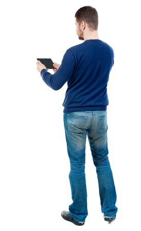 back view of business man uses mobile phone. bearded man in blue pullover horizontally holding the plate.