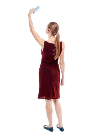 back view of standing young beautiful woman using a mobile phone. Isolated over white background. The girl in the maroon sleeveless dress makes selfie.