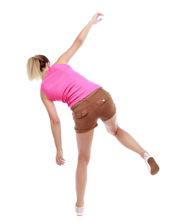 stumble: Balancing young woman. Isolated over white background. Sport blond in brown shorts fall to the side.