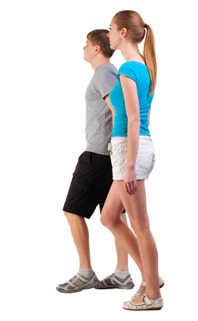 Back view of going young couple (man and woman). walking beautiful friendly girl and guy in shorts together. Rear view people collection.  newlyweds go on a journey. backside view of person.  Isolated over white background. Stock Photo