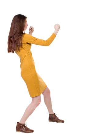 skinny woman funny fights waving his arms and legs. Rear view people collection.  backside view of person.  Isolated over white background. Girl dress in mustard in a fight. Stock Photo
