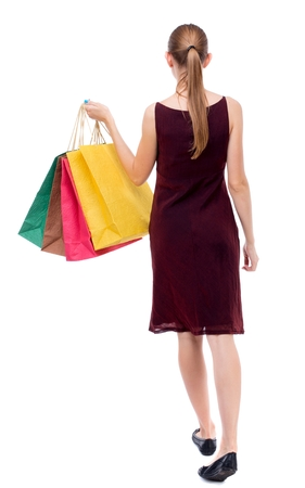 sleeveless dress: back view of going woman with shopping bags Isolated over white background. The girl in the maroon sleeveless dress holding shopping bags.