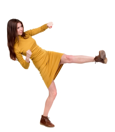 skinny woman funny fights waving his arms and legs. Long-haired brunette in a mustard-colored leg raised high.