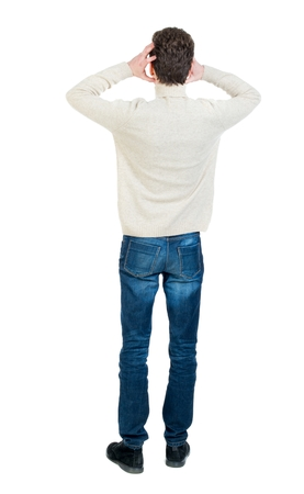 Back view of man . Standing young guy. Rear view people collection. Curly short-haired man in a woolen white jacket in terror clutching at his head.