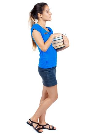 falda corta: Chica viene con la pila de libros. vista lateral. Vista posterior recogida de las personas. chica en una falda corta y una camiseta azul lleva una pila de libros.