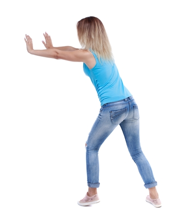 pushes: back view of woman pushes wall. Isolated over white background. blonde in a blue shirt and jeans, put her hands on the wall.