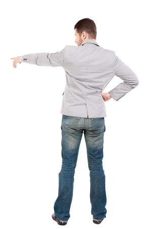 instructs: Back view of pointing business man. guy in a gray jacket instructs.