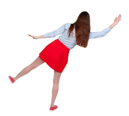 stumble: Balancing young woman. or dodge falling woman. Long-haired brunette in red skirt falls to the side.