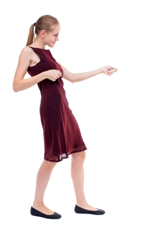 girl in burgundy dress: back view of standing girl pulling a rope from the top or cling to something. Isolated over white background. A girl in a burgundy dress clings to the rope.