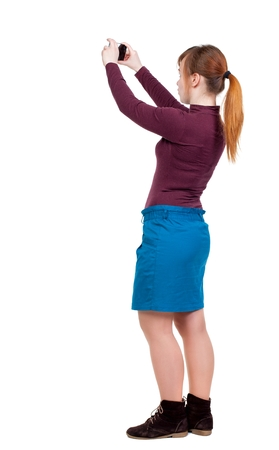 back view of standing young beautiful woman and using a mobile phone. girl watching. Girl with red hair tied in a ponytail relieves phone.