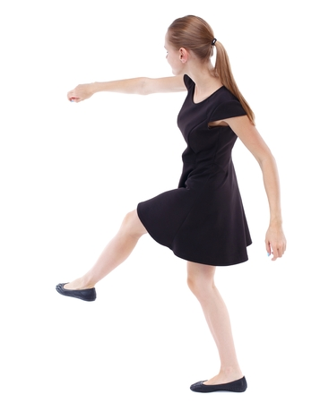 skinny woman funny fights waving his arms and legs. Blonde in a short black dress kicking ball Stock Photo