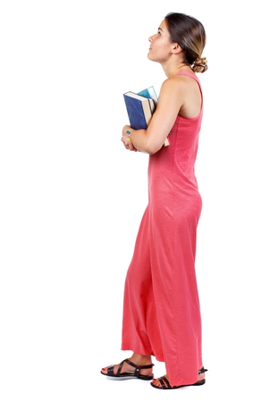 Girl comes with stack of books. side view. backside view of person. Isolated over white background. A slender woman in a long red dress carries a book and looking up. Stock Photo