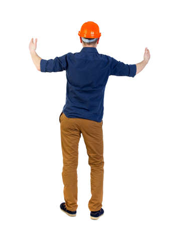 Back view of builder in helmet shows thumbs up. engineer in a blue shirt with the sleeves rolled up and a helmet holds out his hands in greeting.