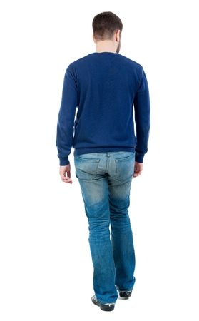 Back view of going handsome man. bearded man in blue pullover is looking to the side.
