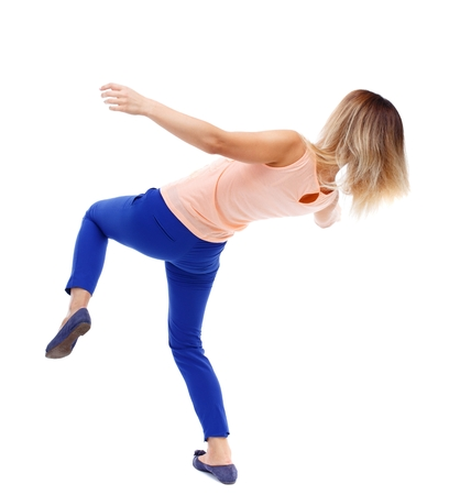 stumble: Balancing young woman. or dodge falling woman. Rear view people collection. blonde in a pink t-shirt falls on its side. Stock Photo