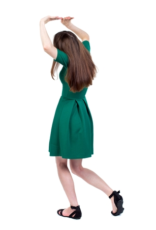 back view of woman protects hands from what is falling from above. The slender brunette in a green short-crossed her arms over her head. Stock Photo