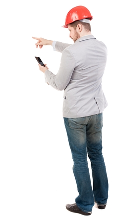instructs: Backview of business man in construction helmet stands and enjoys tablet or using a mobile phone. guy in a gray jacket and an orange helmet instructs reading with telf... Stock Photo