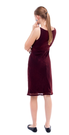 girl in burgundy dress: back view of standing young beautiful woman. girl in a burgundy dress sleeveless thoughtful touches his face.
