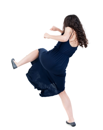 skinny woman funny fights waving his arms and legs. dark curly girl in blue evening dress kicks.