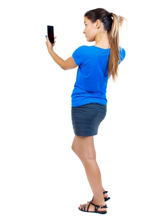 black and white photograph: back view of standing young beautiful woman using a mobile phone. girl watching. girl in a short skirt and a blue T-shirt uses the phone as a mirror. Stock Photo
