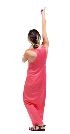 back view of standing girl pulling a rope from the top or cling to something. A slender woman in a long red dress shows thumb up raising his arm above his head. Stock Photo