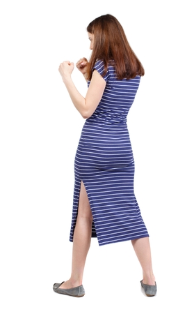 wimp: skinny woman funny fights waving his arms and legs. brunette in a blue striped dress standing sideways in a boxing rack.