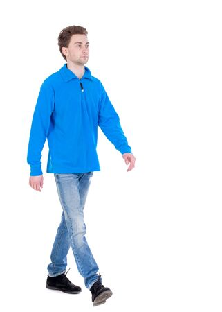 treading: front view of going handsome man. walking young guy . Curly boy in the blue jacket proudly moving forward. Stock Photo