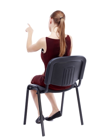 girl in burgundy dress: back view of young beautiful woman sitting on chair and pointing. girl in a burgundy dress sitting on a chair selects an answer.