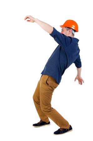 hombre cayendo: Equilibrio joven. o esquivar el hombre que cae. trabajador de la construcción del casco cae. Ingeniero en casco protector cae agitando los brazos.