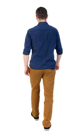 Back view of going handsome man. walking young guy . man in a blue shirt with the sleeves rolled out into the distance