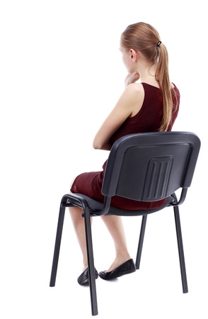 back view of young beautiful woman sitting on chair. girl watching. Isolated over white background. A girl in a burgundy dress sitting on a chair listening intently. Stock Photo