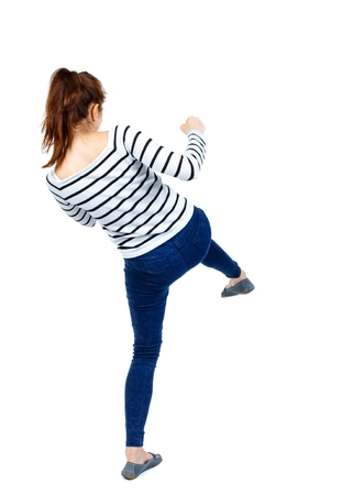 hits: back view of woman funny fights waving his arms and legs. Rear view people collection. Girl in a striped sweaters back and hits his foot. Stock Photo