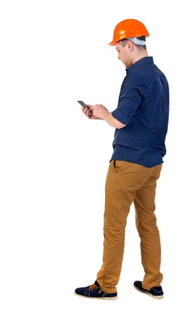 backview: Backview of business man in construction helmet stands and enjoys tablet or using a mobile phone. man in a blue shirt and a helmet uses a smartphone. Stock Photo