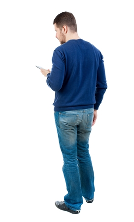 back view of business man uses mobile phone. bearded man in blue pullover looks to the smartphone. Stock Photo