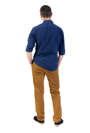 his shirt sleeves: Back view of man . Standing young guy. man in a blue shirt with the sleeves rolled up, standing with his hands in his pocket, and looks into the distance. Stock Photo