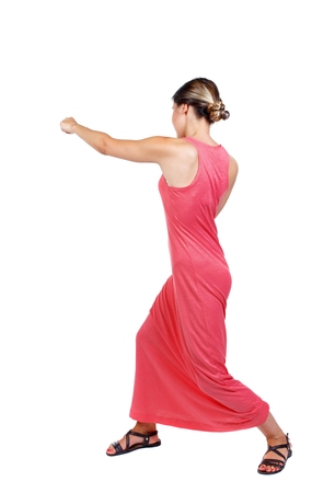 wimp: skinny woman funny fights waving his arms and legs. slender woman in a long red dress strikes a hand. Stock Photo