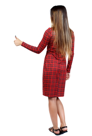 red plaid: Back view of woman thumbs up. girl in red plaid dress shows thumb up.